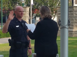 Lynette Drake, interim vice president for student affairs, swears in Joel Stewart as the newest member of EIU's police force.