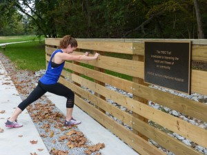 Lauren Hoelscher stretches prior to a run on the new expansion to the TREC Trail off Outer Belt West. HSHS St. Anthony's Memorial Hospital contributed funds to help make the trail expansion possible.