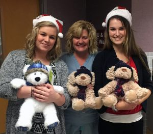 Kay Jewelers employees Megan Cozadd (left) and Darienne Lester (right) pose with Nancy Oberlink, RN, from Women and Children's Care, and some of the approximately 60 stuffed animals Kay Jewelers donated to HSHS St. Anthony's Memorial Hospital on Christmas Eve for pediatric patients.